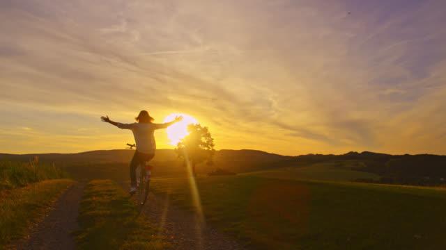 vídeos de stock, filmes e b-roll de slo mo mulher andando de bicicleta com os braços estendidos ao pôr do sol - de braço levantado