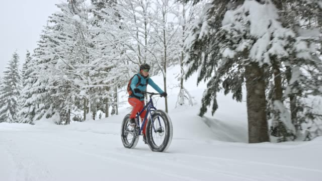 ts woman riding her fat bike on a snowy trail - goggles sportswear stock videos and b-roll footage