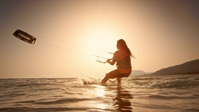 slo mo woman riding her kiteboard at sunset - cádiz stock videos and b-roll footage