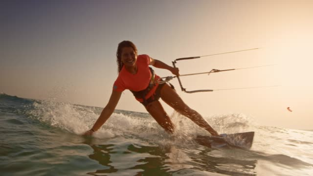 slo mo woman riding her kiteboard with one hand in the water and smiling into the camera at sunset - adventure stock videos & royalty-free footage