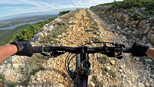 POV Woman riding her mountain bike across a mountain on a rocky road above the sea