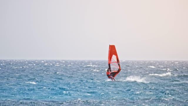 stockvideo's en b-roll-footage met slo mo vrouw rijden haar windsurf op zee - windsurfen
