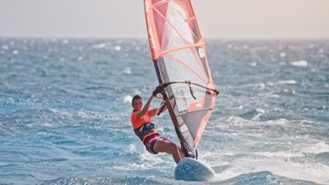 stockvideo's en b-roll-footage met slo mo vrouw rijden haar windsurf met één hand aan de orde gesteld in de lucht en glimlachen - windsurfen
