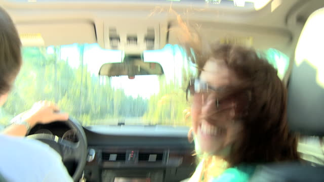 woman riding in a car looking at the camera