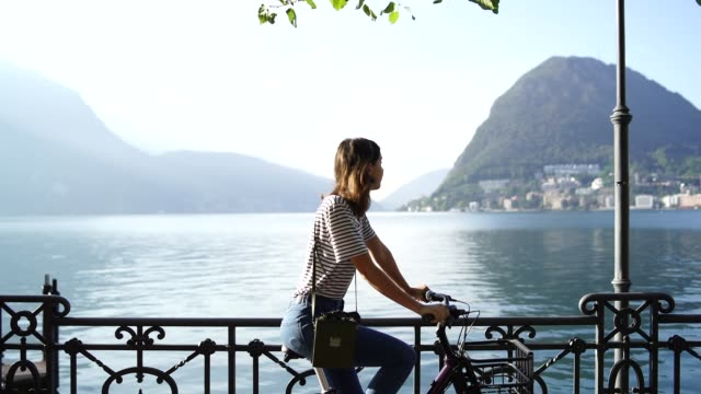 vídeos de stock e filmes b-roll de woman riding on a bicycle along a scenic lakeside - switzerland