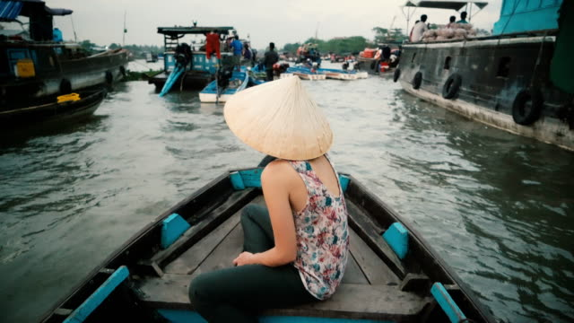woman riding on boat through mekong delta - traditionally vietnamese stock videos & royalty-free footage
