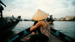 Woman riding on boat through Mekong delta