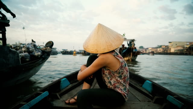 woman riding on boat through mekong delta - reportage stock videos & royalty-free footage