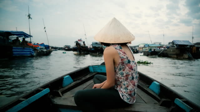 woman riding on boat through mekong delta - vietnam stock videos & royalty-free footage