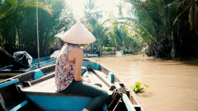 vidéos et rushes de femme à cheval sur le bateau dans le delta du mékong - vietnam