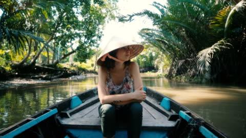 vidéos et rushes de femme à cheval sur le bateau dans le delta du mékong - transport nautique