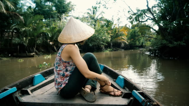 woman riding on boat through mekong delta - mekong delta stock videos & royalty-free footage