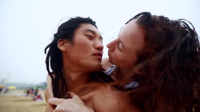 cu slo mo woman riding piggyback on man shoulders at daecheon beach / boryeong, chungcheongnam-do, south korea - south korea couple stock videos & royalty-free footage