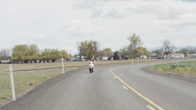 Woman riding scooter down country road on a sunny day