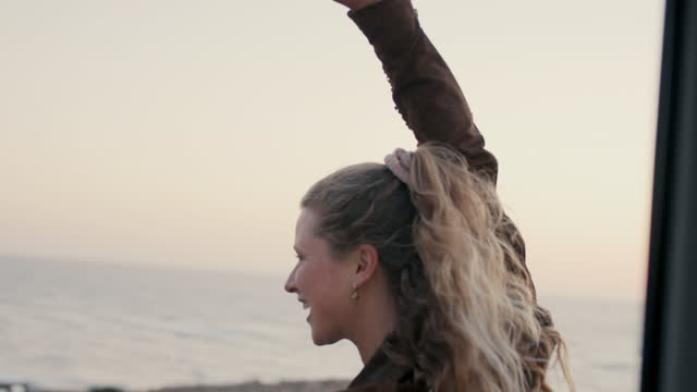 stockvideo's en b-roll-footage met woman riding skateboard by sea holding on to car - rondrijden