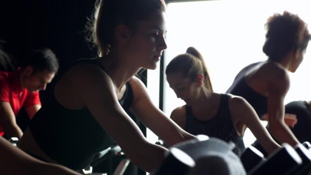 ms r/f woman riding stationary bike during fitness class in cycling studio - 30 34 ��r bildbanksvideor och videomaterial från bakom kulisserna