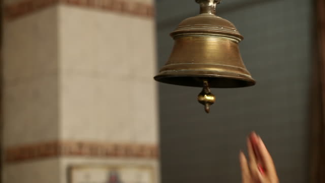 Woman ringing bell of a temple