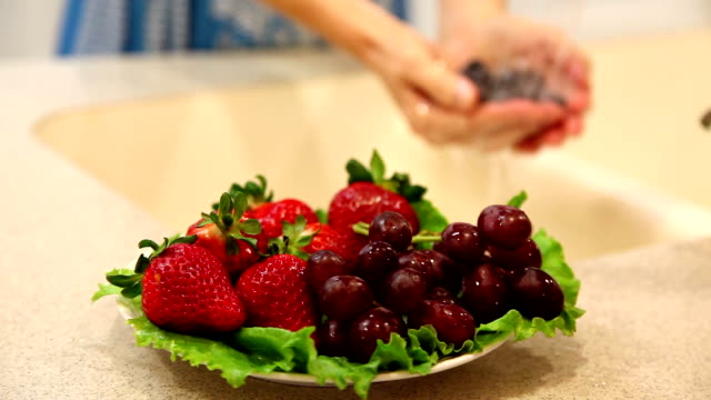 Woman rinses blueberry fruits in home kitchen sink.