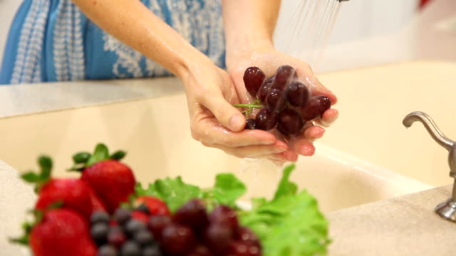 Woman rinses red grapes in home kitchen sink.