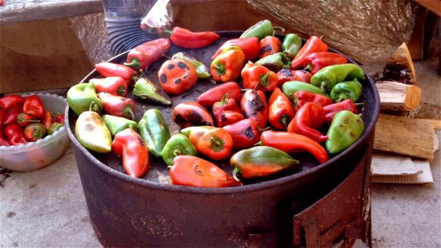 Vrouw in rode en groene paprika's roosteren