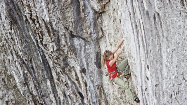 tu woman rock climbing and securing herself by pulling a rope through the quickdraw - climbing rope stock videos & royalty-free footage