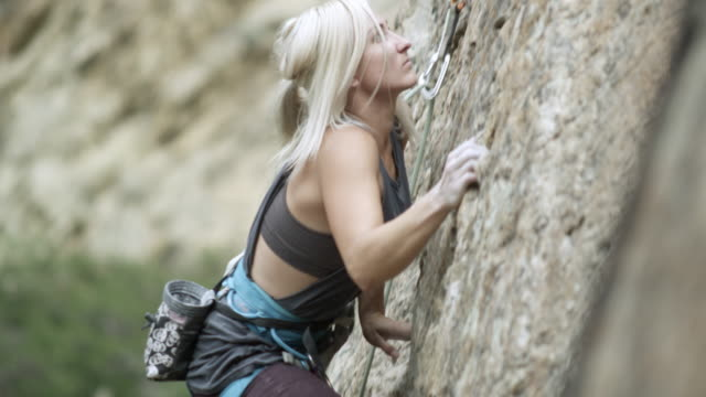 vídeos de stock e filmes b-roll de woman rock climbing and topping out. - corda de trepar
