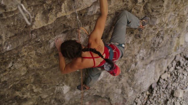 Woman rock climbing in cave switching rope to carabiner / American Fork Canyon, Utah, United States