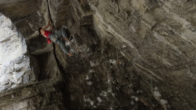 woman rock climbing on ceiling of cave / american fork canyon, utah, united states - american fork canyon stock videos & royalty-free footage