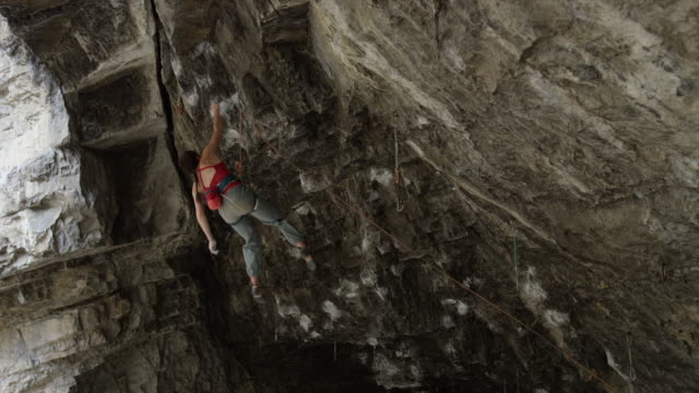 woman rock climbing on ceiling of cave / american fork canyon, utah, united states - american fork canyon stock videos and b-roll footage