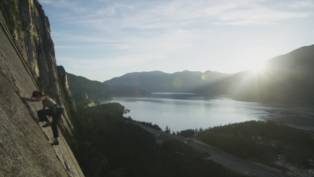 ws ha woman rock climbing on cliff with coastline in background, squamish, british columbia, canada - british columbia stock videos & royalty-free footage