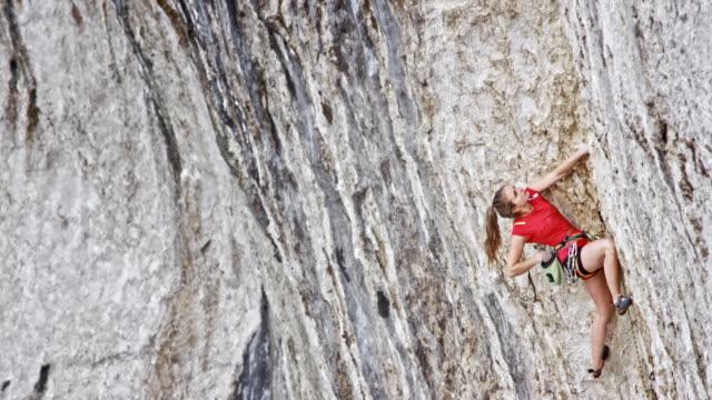 TD Woman rock climbing up a cliff
