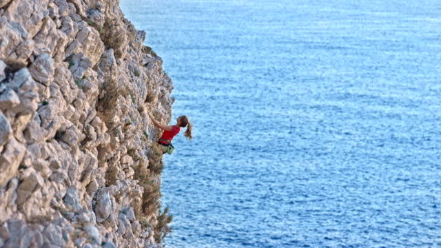 Woman rock climbing up a jagged cliff above the sea in setting sun