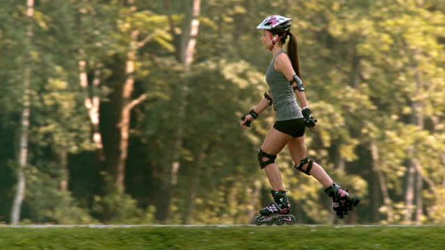 slo mo ts woman roller skating in the park - elbow pad stock videos & royalty-free footage