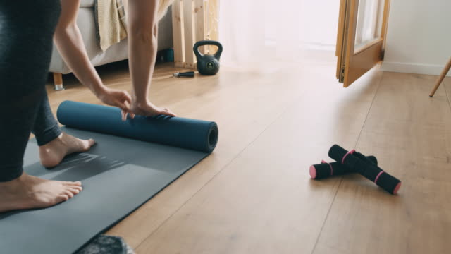 slo mo woman rolling back the exercise mat after exercising at home - exercise room stock videos & royalty-free footage