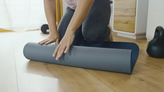 slo mo woman rolling back the exercise mat - exercise room stock videos & royalty-free footage