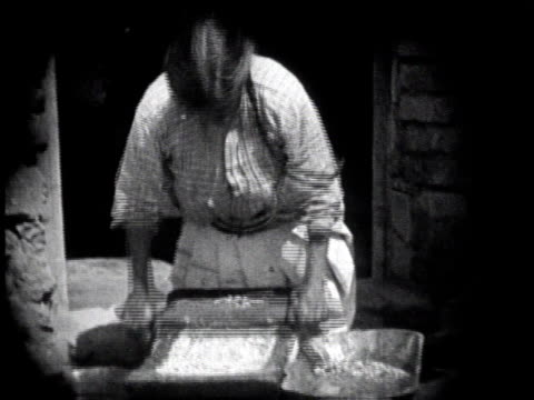 1930 MONTAGE Woman rolling grains into dough with rolling pin / Mexico City, Mexico