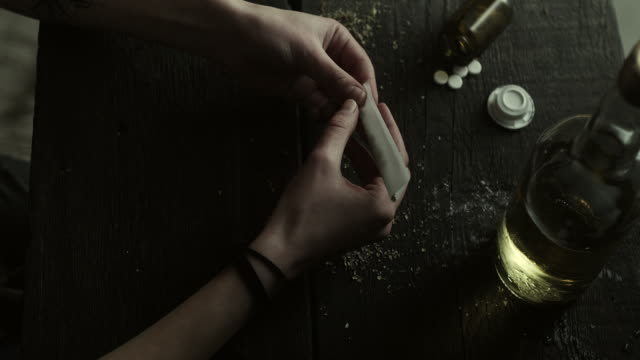 woman rolling marijuana joint - addiction stock videos and b-roll footage