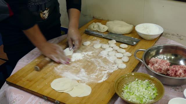 vídeos y material grabado en eventos de stock de a woman rolling out dumpling skin - esmalte de uñas rojo