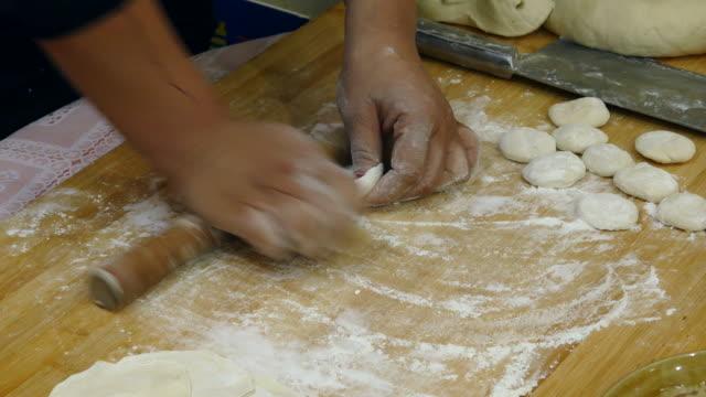 vídeos de stock, filmes e b-roll de a woman rolling out dumpling skin - rolo de pastel