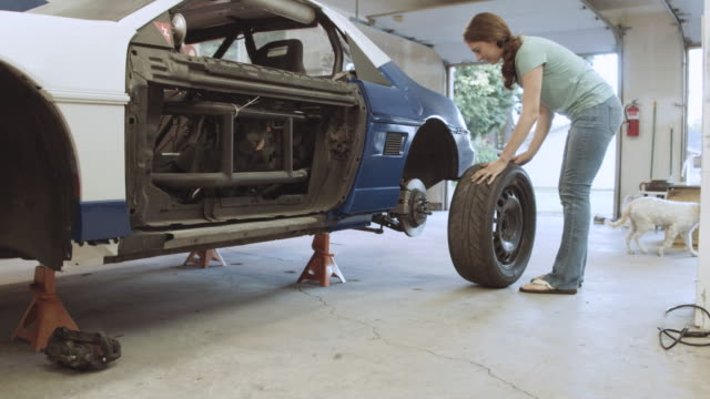 Woman rolling tire over to install on her vehicle