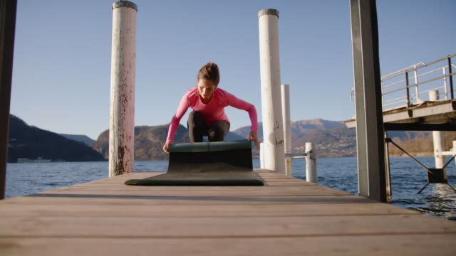 woman rolling up yoga mat - one mature woman only stock videos & royalty-free footage