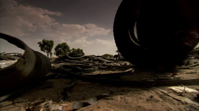 vídeos de stock, filmes e b-roll de a woman rolls a tyre along the ground. - b roll