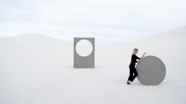 vidéos et rushes de woman rolls circular portal in desert - endroit isolé