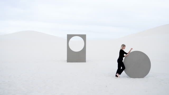 vídeos de stock, filmes e b-roll de woman rolls circular portal in desert - etnia caucasiana
