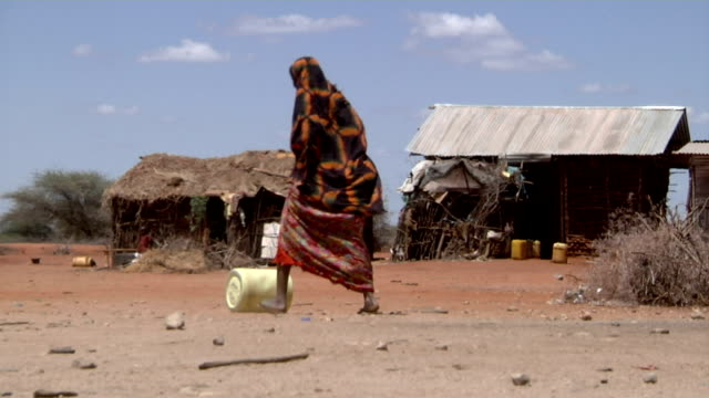 woman rolls water canister in village on august 02 2011 in garisa kenya - bombola video stock e b–roll