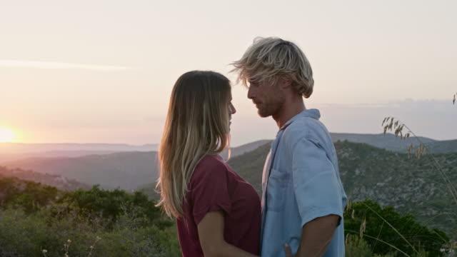 vídeos de stock e filmes b-roll de woman romancing with boyfriend during sunset - beijar