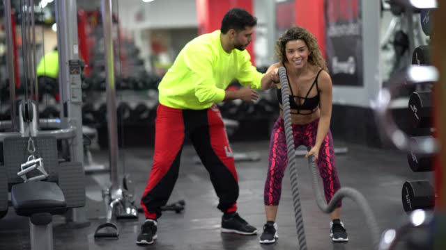 Woman rope lifting and a personal instructor correcting her posture