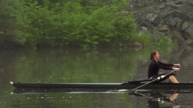 ws pan woman rowing in single scull on the connecticut river at dawn/ hanover, new hampshire, usa - scull stock videos & royalty-free footage
