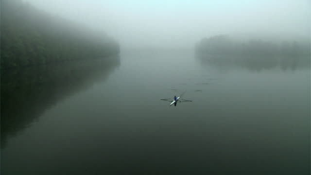 ha ws woman rowing past in single scull on the connecticut river in fog at dawn/ hanover, new hampshire, usa - scull stock videos & royalty-free footage