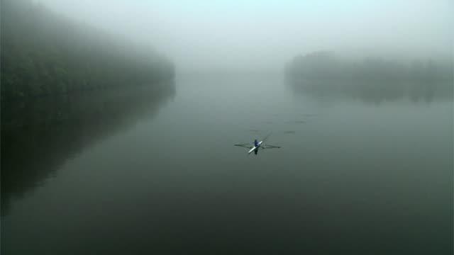 vídeos y material grabado en eventos de stock de ha ws woman rowing past in single scull on the connecticut river in fog at dawn/ hanover, new hampshire, usa - remo con espadilla